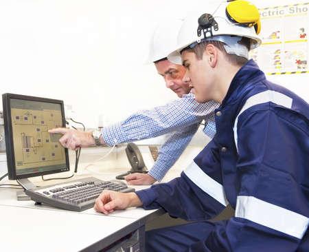 Äldre och yngre ingenjörer diskuterar arbete tillsammans på kontoret, senior man pekar på skärmen