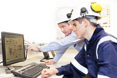 work together: Senior en junior engineers bespreken werken samen in het kantoor, senior man wijzend op scherm