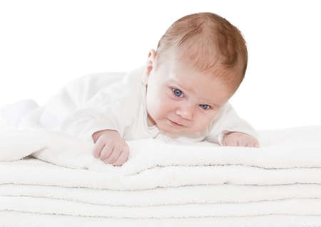 Happy healthy newborn baby boy with blue eyes is lying crawling on a pile of towels photo