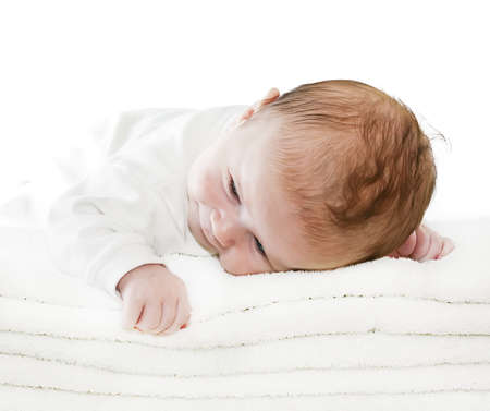 Happy healthy newborn baby boy with blue eyes is lying crawling on a pile of towels Stock Photo
