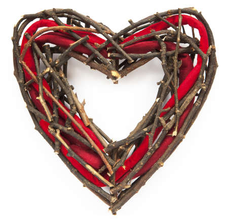 Closeup of heart-shaped christmas or St. Valentine wicker wreath with red felt. Square crop isolated on white