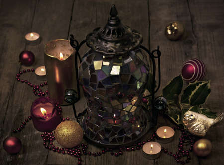 Still life of Christmas ornaments on old wooden floor with lit candles and dim light photo