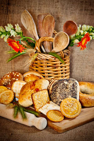 Various baked goods with a cutting board, wooden utensil and cereal ears Stock Photo - 17172152