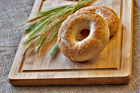 Two bagels on bread board with wheat corns on old sack cloth. Still life Stock Photo - 17172150