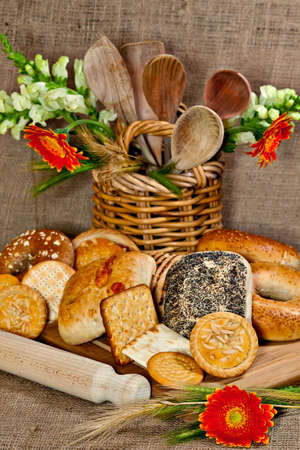 Various baked goods with a cutting board, wooden utensil and cereal ears Stock Photo - 17245371