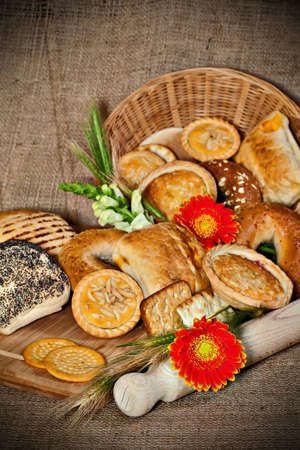 Various baked goods with a cutting board, wooden utensil and cereal ears Stock Photo - 17245370