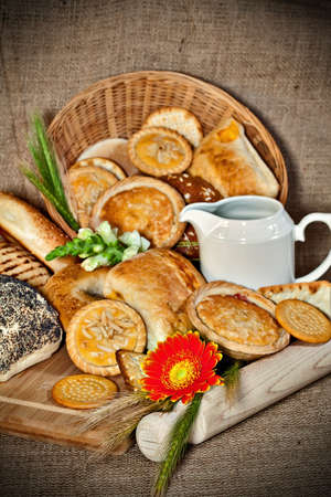 Various baked goods with a cutting board, wooden utensil and cereal ears Stock Photo - 17245366