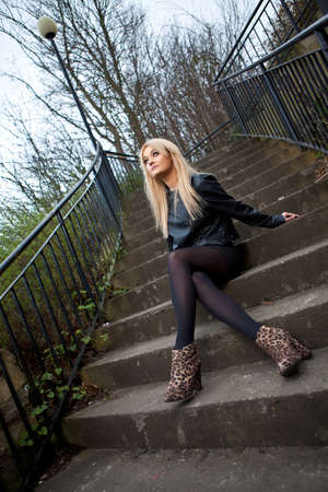 jacked: Portrait of young blonde caucasian woman dressed in leather jacket and short scirt.  Stock Photo