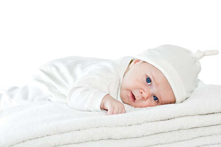 Happy healthy newborn baby boy with blue eyes is lying crawling on a pile of towels and looking at us. Studio isolated on white background. Closeup. Look at my other baby shots in different situations photo