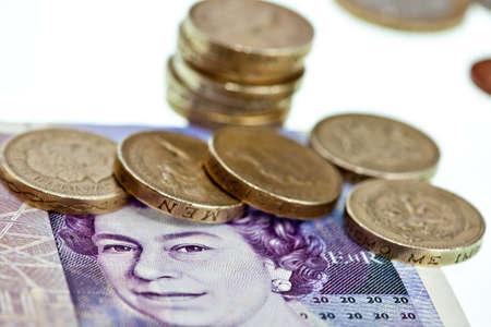 Brittiska pund i sedlar och mynt makro isolerade på vit Stockfoto
