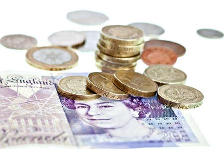 Britannico sterlina in monete e banconote macro isolato su bianco