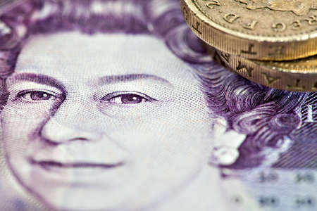 gbp: Closeup of Queen on 20 british pounds note with one pound coins Stock Photo
