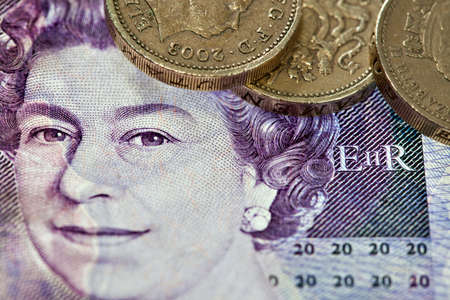 Closeup of Queen on 20 british pounds note with one pound coins photo