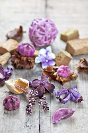 Close-up of aromatic dried flowers and other natural things on wooden surface. Potpourri used for aromatherapy. Selective focus