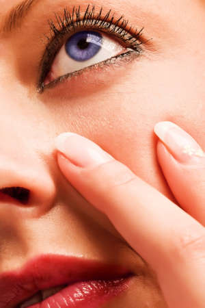 Closeup of a caucasian sensual girl's face with blue eyes and fingers with manicure Stock Photo - 18785508