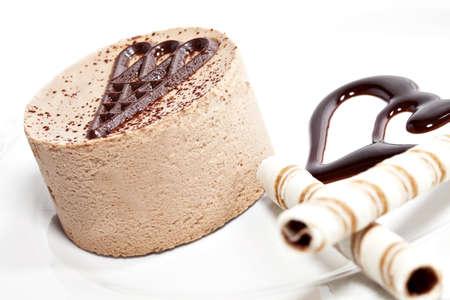Chokladmousse på tallrik dekorerad med två kaka pinnar. På vit platta
