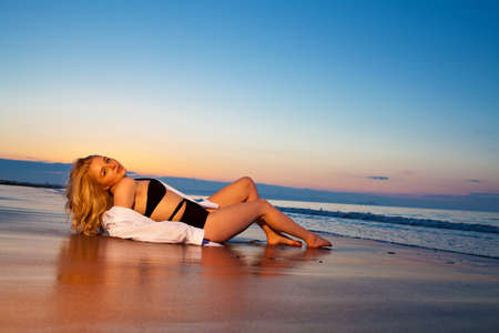 Beautiful dreamy lonely blonde girl lying on the beach against dusk blue sky. More images of this model in my portfolio photo