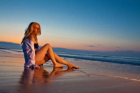 Beautiful dreamy lonely blonde girl sitting on the beach against dusk blue sky. More images of this model in my portfolio photo