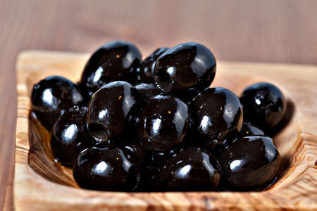 pitted: Closeup of Black pitted marinated olives in olive tree dish on wooden table Stock Photo