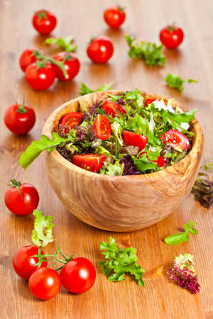 Bowl made of olive wood filled with mixed lettuce salad and cherry vine tomatoes on wooden table. More healthy food in my portfolio Stockfoto
