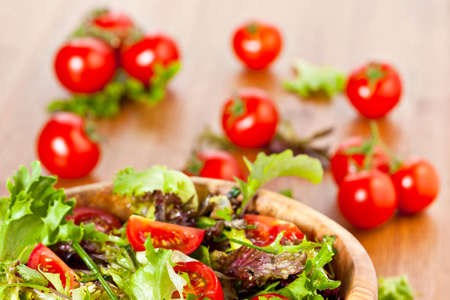 Bowl made of olive wood filled with mixed lettuce salad and cherry vine tomatoes on wooden table. More healthy food in my portfolio photo