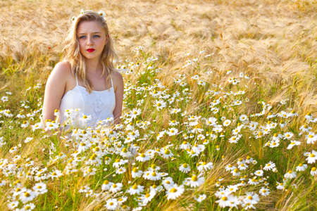 Blond beautiful girl at camomile field, pretty looking woman on meadow of daisy flowers, cute young lady relaxing outdoor, having fun,  joyful young female and summer green nature, harmony concept  photo