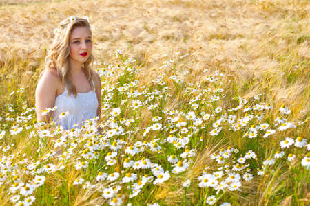 Blond beautiful girl at camomile field, pretty looking woman on meadow of daisy flowers, cute young lady relaxing outdoor, having fun,  joyful young female and summer green nature, harmony concept