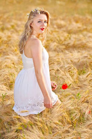 Portrait of pretty young woman at wheat field, a girl against golden wheat background expressing calmness emotions photo