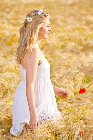 unconcerned: Retrato de mujer joven y bonita en el campo de trigo, una ni�a contra el fondo de oro del trigo expresar emociones calma