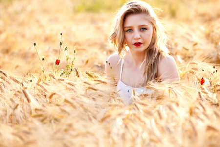 unconcerned: Portrait of pretty young woman at wheat field, a girl against golden wheat background expressing calmness emotions Stock Photo