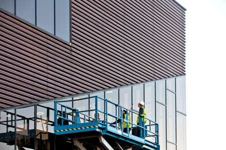 Builder on a Scissor Lift Platform at a construction site. Men at work Imagens