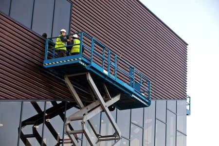 Builder on a Scissor Lift Platform at a construction site. Men at work Stock Photo