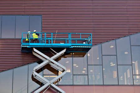 Builder på Scissor Lift Plattform på en byggarbetsplats. Män i arbetet