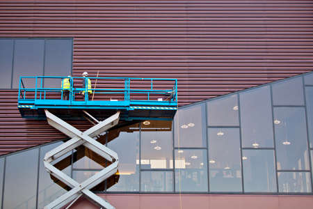 Builder on a Scissor Lift Platform at a construction site. Men at work photo