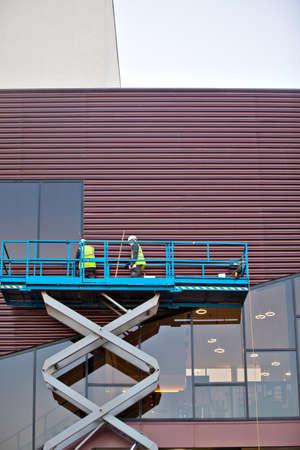 Builder on a Scissor Lift Platform at a construction site. Men at work photo