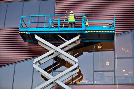 Builder on a Scissor Lift Platform at a construction site. Men at work Stock Photo