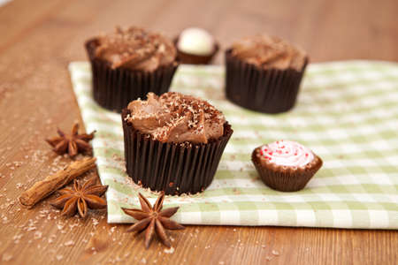 Lovely fresh chocolate cupcakes on greeen cloth. Very shallow depth of field  photo