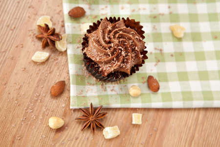Above view of lovely fresh chocolate cupcake on greeen cloth. Very shallow depth of field  photo