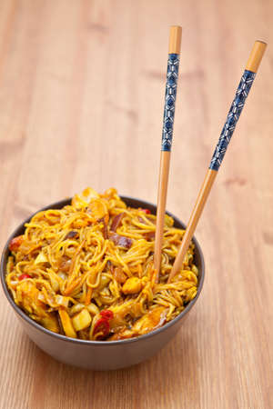 Brown ceramic bowl with a portion of Singapore noodles photo
