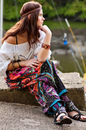 Pretty young hippie caucasian girl in motley boho fashion style outfit photo