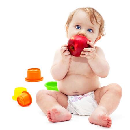 Söt liten kaukasiska pojke 11 månader gammal sitter och äter rött äpple på vit bakgrund