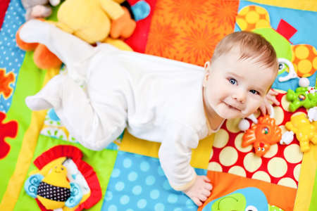 Closeup of happy six months baby boy crawling on colorful playmat photo