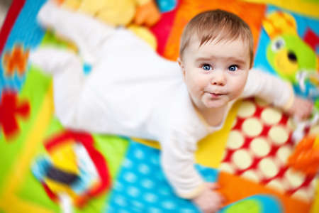 playmat: Closeup of happy six months baby boy crawling on colorful playmat