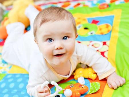 Close-up van gelukkige zes maanden baby boy kruipen op kleurrijke speeltapijt