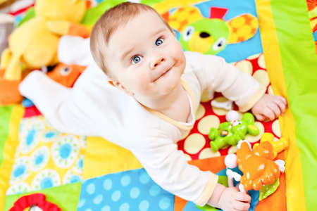 six months: Closeup of happy six months baby boy crawling on colorful playmat