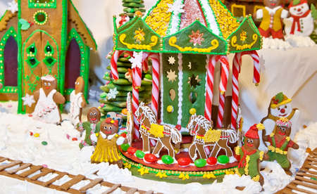 happy gingerbread people gathered by the christmas tree and carousel as christmas fun decoration stock photo