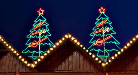 Neon lights illuminated Christmas tree on wooden triangle roof of German market