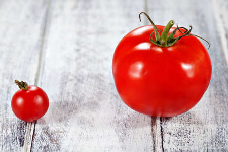 Cherry and normal tomatoes on white painted table surface photo