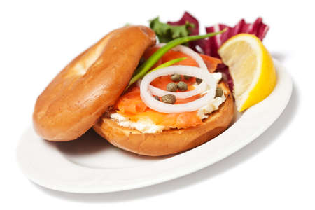 Close-up of delicious snack. Salmon Bagel Sandwich on white plate isolated on white background photo
