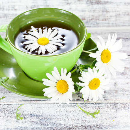 Closeup of a cup with herbal chamomile tea served in green ceramic cup and few wild flowers on white painted wooden surface photo